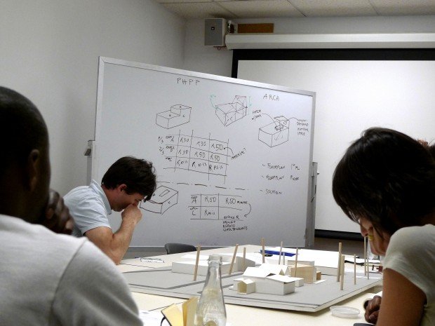 The image here shows a group of students very intently working together on passive house standards of our house.