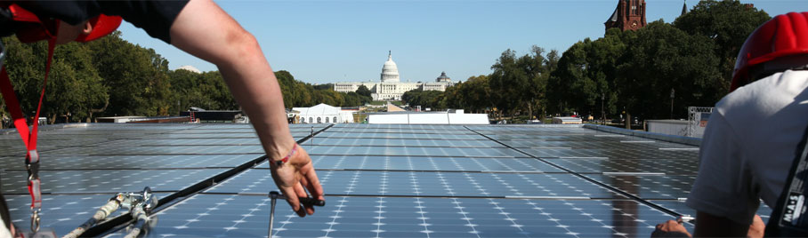 An image of solar panels on the national mall, two students are working on a roof in view of the capitol.