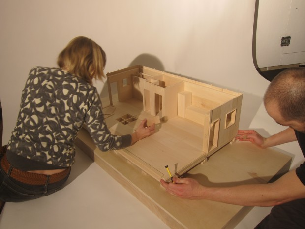 two students work on a large scale basswood model